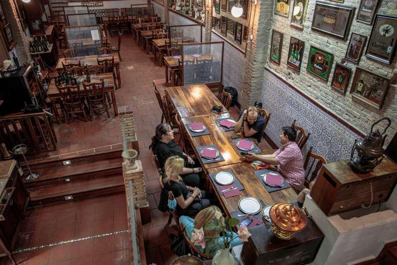 En la imagen, varias personas comen en el interior de un restaurante.