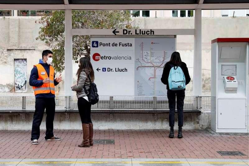 Uno de los auxiliares COVID-19 de Ferrocarrils de la Generalitat Valenciana (i) (FGV) informa a una usuaria de Metrovalencia sobre el control de aforo en trenes y tranvías y las medidas de prevención adoptadas en el transporte público frente a la pandemia. EFE/Ana Escobar.