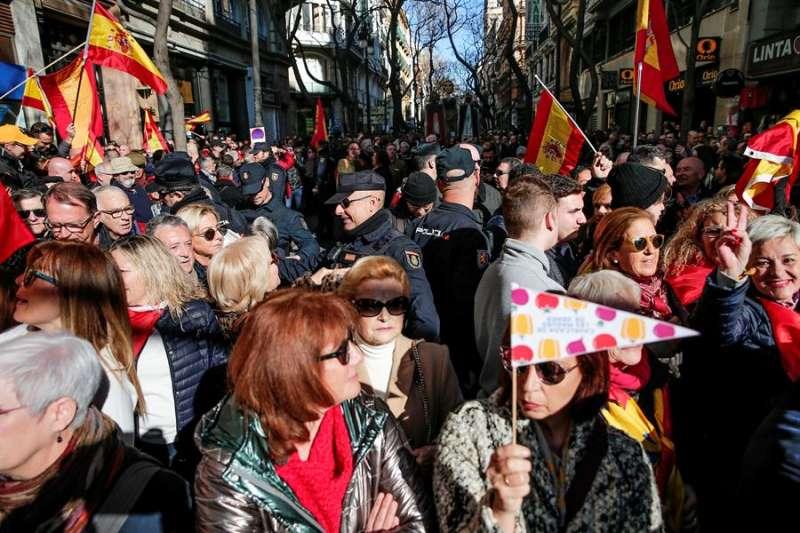 Agentes de la Policía Nacional establecen un cordón para proteger la cabalgata de las Magas de Enero a su llegada a la plaza del Ayuntamiento, tras el intento de boicot por parte de varias personas que venían de la concentración convocada por Vox. EFE/Manuel Bruque
