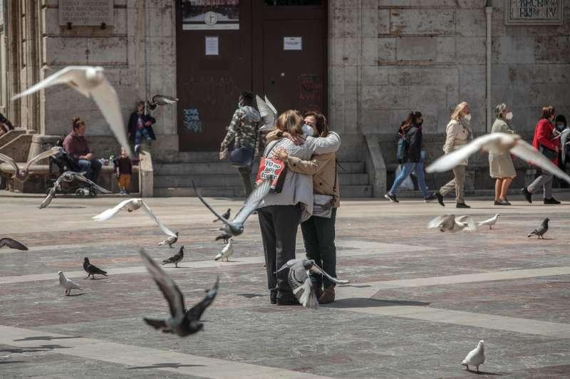 Dos personas se abrazan en una céntrica plaza de València. EFE