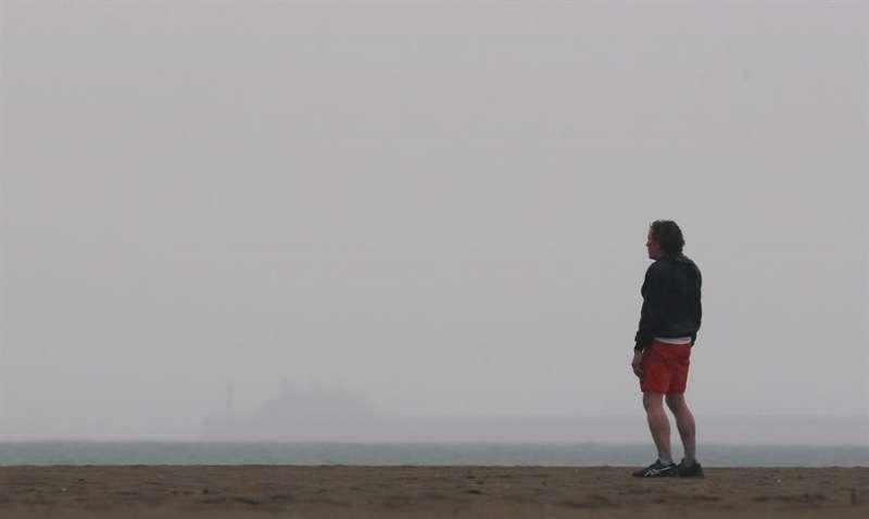 Un hombre contempla el mar cubierto de bruma en una playa de València. EFE/Kai Försterling