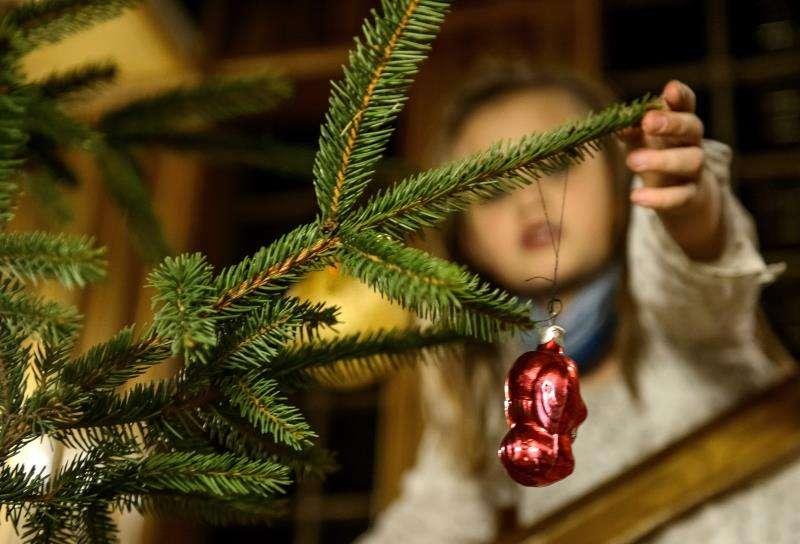 Una niña coloca un adorno navideño en un árbol. EFE/Archivo