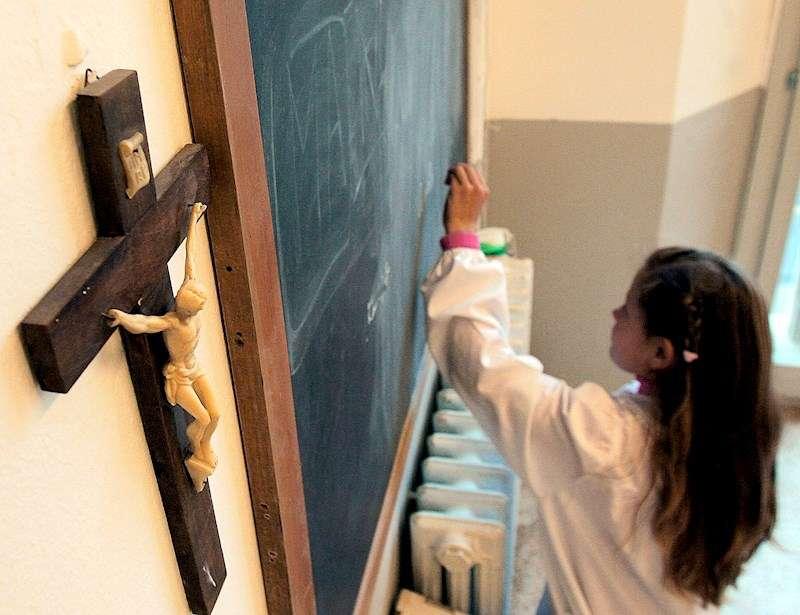 Foto de archivo de una estudiante en una clase adornada con un crucifijo en un colegio. EFE/Archivo