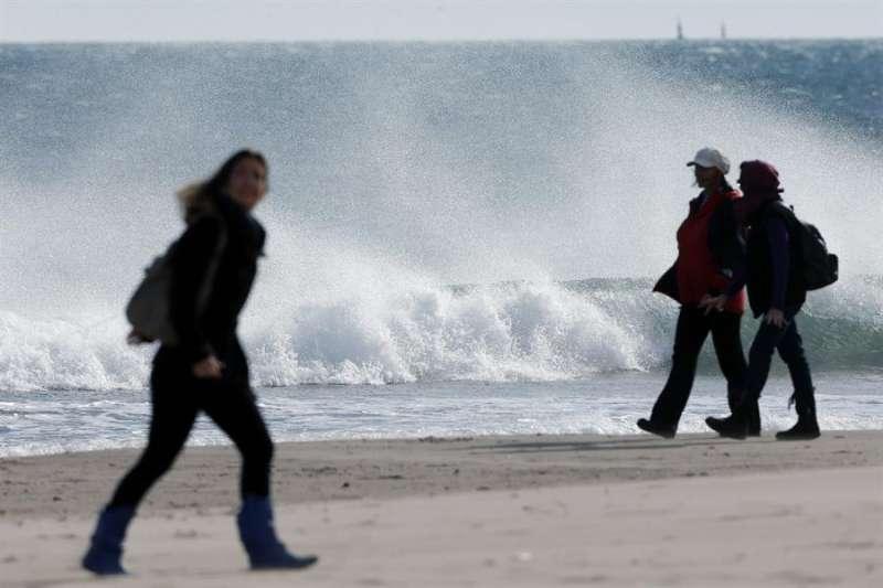 Dos personas pasean por la playa en un día de fuerte viento. - EFE