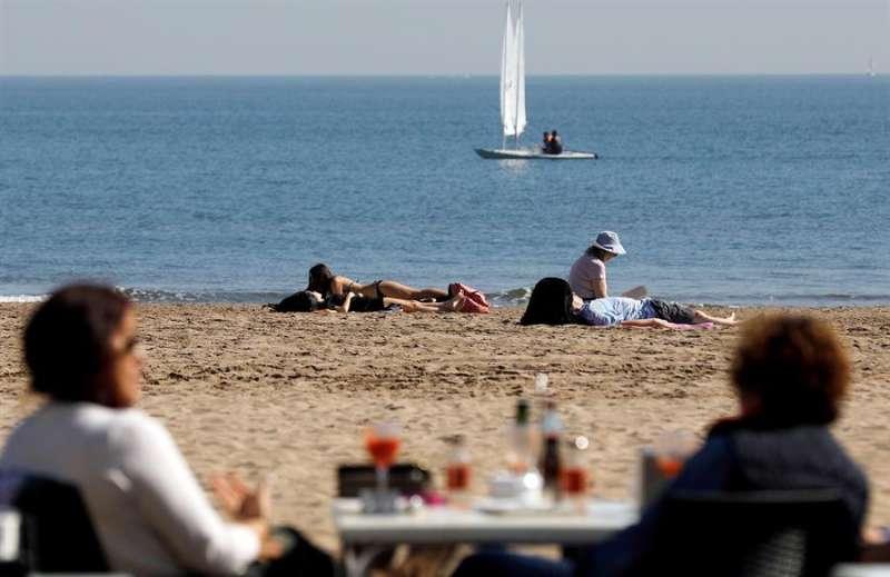 Varias personas disfrutan del buen tiempo y de las altas temperaturas en la playa de la Malvarrosa. EFE/Kai Försterling