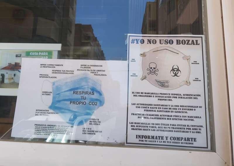 Dos carteles en la puerta de la inmobiliaria.