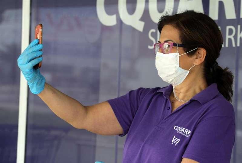 Una mujer con mascarilla realiza una videollamada. EFE/Archivo