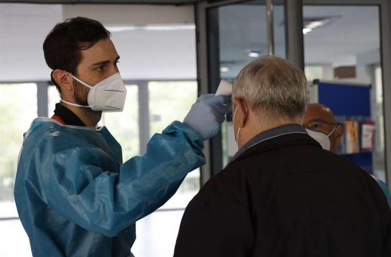 Personal sanitario toma la temperatura a una persona en la entrada a un centro de mayores. EFE/Zipi/Archivo