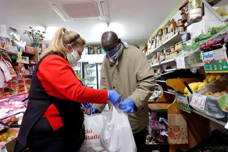 Mayte ayudando a uno de los inmigrantes del barrio. EFE