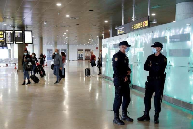 Dos agentes de la Policia Nacional vigilan la puerta de llegadas del aeropuerto de València. efe