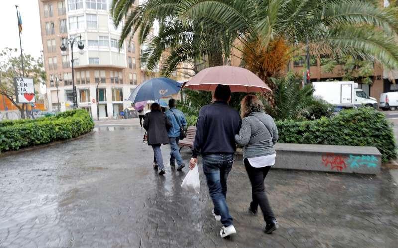 Varias personas pasean protegidas con paraguas por el centro de Val�ncia. EFE/Manuel Bruque/Archivo