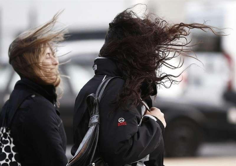 Dos jóvenes pasean por la calle en una jornada marcada por el fuerte viento. EFE/Archivo