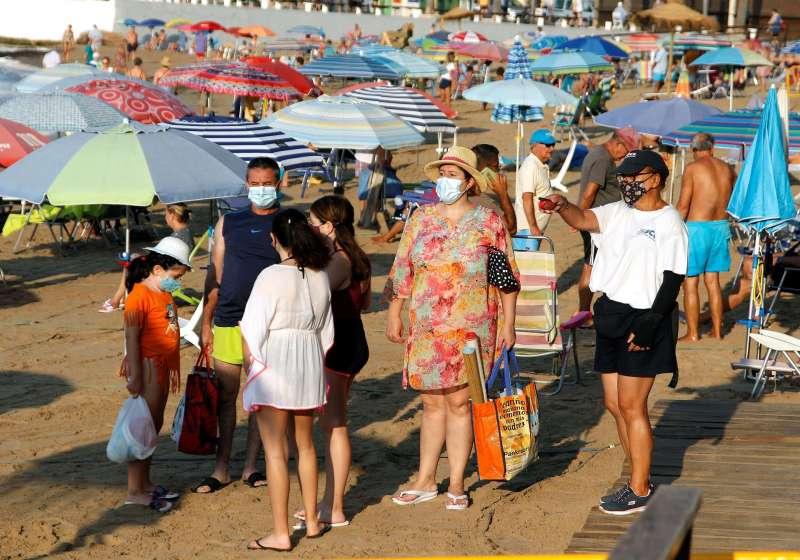 Un grupo de turistas se dispone a pasar un día en la playa del Cura de Torrevieja (Alicante).