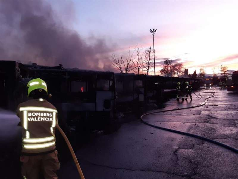 Bomberos refrescando los vehículos quemados. EFE