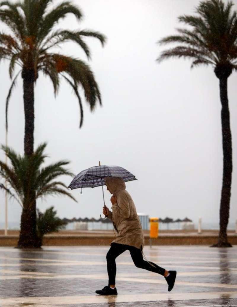 Una joven se protege con un paraguas en esta jornada de lluvia. EFE
