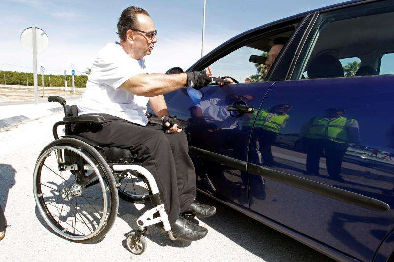 Manuel Marcos, de la Asociación de personas con lesión medular y otras discapacidades físicas (Aspaym), informa a un conductor acerca de la campaña