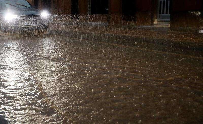 Un vehículo circula por una calle anegada de Valencia durante la tarde de hoy en la que el fuerte temporal de lluvias que afecta este jueves a la Comunitad Valenciana ha dejado 87,9 litros por metro cuadrado (l/m2) en la capital, Valencia, y hasta 60,4 l/m2 en un acumulado registrado en cuatro horas, según los datos ofrecidos por la Agencia Estatal de Meteorología (Aemet) y la Confederación Hidrog