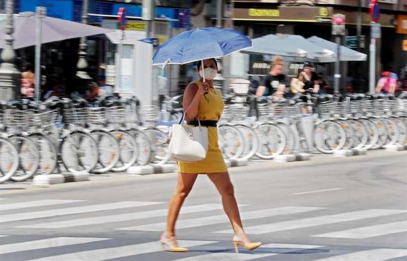 Una persona se protege del calor con una sombrilla. EFE/Kai Försterling