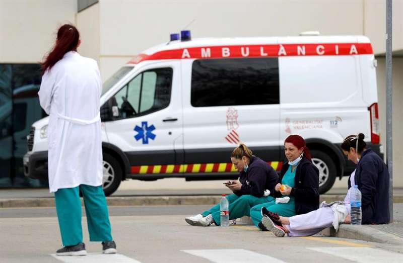 Personal sanitario del Hospital La Fe de Valencia descansa unos minutos ante la puerta de urgencias. EFE/Manuel Bruque/Archivo