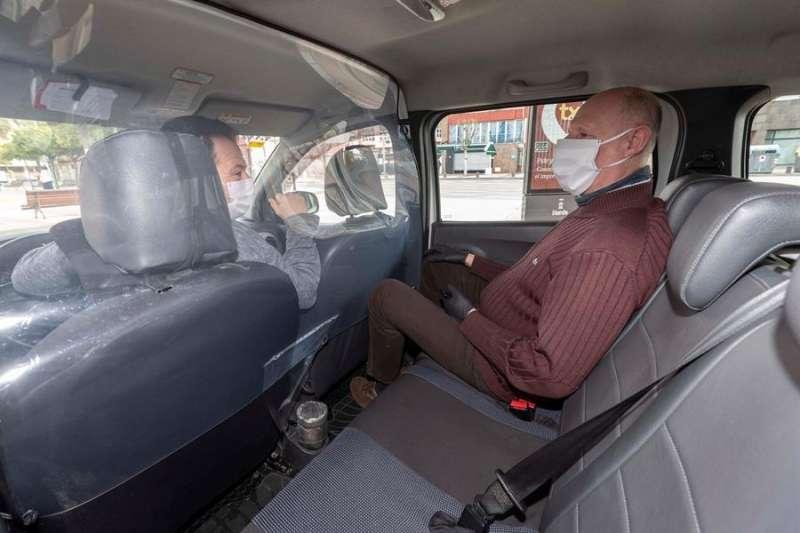 Un usuario del taxi conversa con el taxista a través de la mampara que han tenido que colocar en los vehículos a causa del coronavirus. EFE