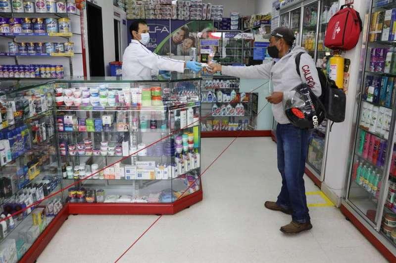 Dos hombres con mascarilla en una farmacia. EFE/Archivo