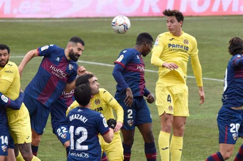 El defensa del Villarreal, Pau Torres (2d) trata de rematar un balón en el partido Huesca-Villarrea