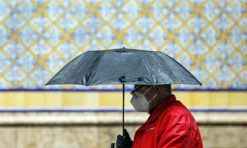 Un hombre se protege con un paraguas de la lluvia durante el pasado 15 de abril, el trigésimo segundo día del estado de alarma. EFE/Ana Escobar