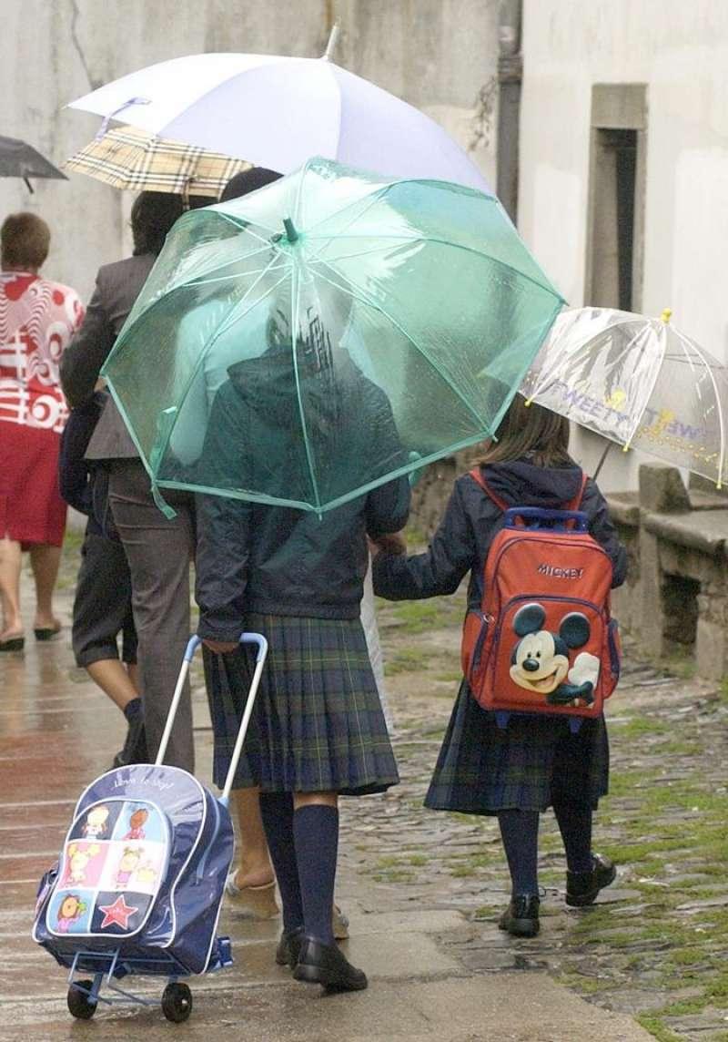 En la imagen, un grupo de niños va al colegio con paraguas. / EFE