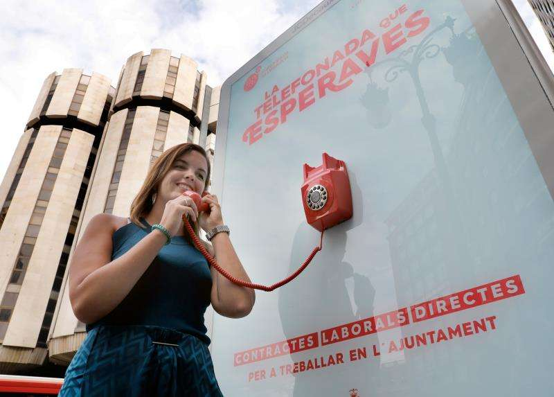 Más de una quincena de empresas contratarán en València a mayores de 55 años. La concejala de Desarrollo Sostenible, Sandra Gómez, junto a la cabina telefónica instalada para informar a quien lo descuelgue sobre programas de empleo para mayores de 55 años. EFE/ Archivo