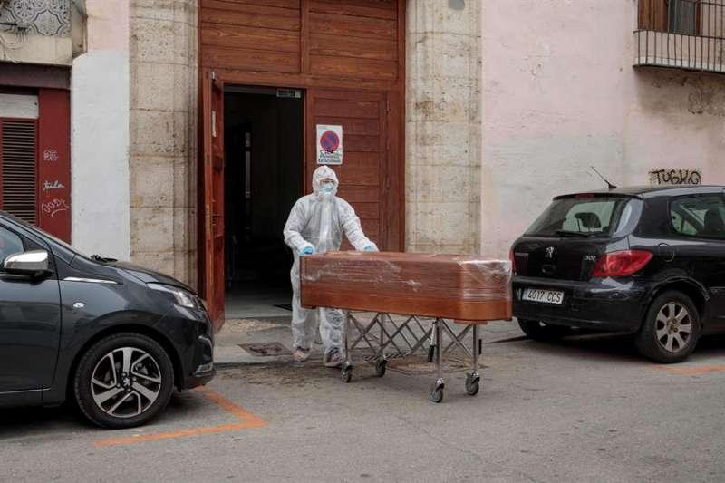 Un operario de la funeraria traslada el féretro al vehículo. EFE
