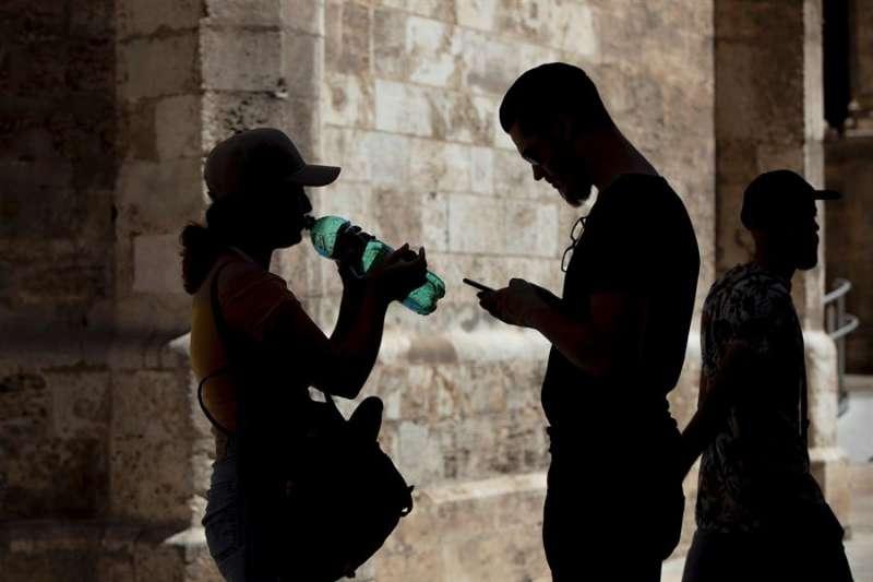 Una mujer bebe agua de una botella en el centro histórico de València en una imagen de archivo. EFE/Biel Aliño/Archivo