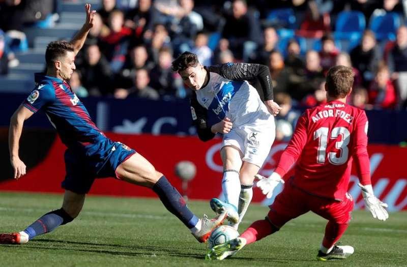 Nemanja Radoja (i) y el guardameta Aitor Fernández (d) del Levante, tratan de repeler el disparo del centrocampista Borja Sainz del Deportivo Alavés. EFE/Kai Försterling