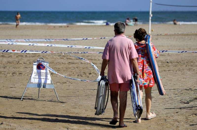 Dos bañistas pasan junto a una señal que informa de la prohibición de bañarse en una de las playas de La Pobla de Farnals (Valencia). EFE