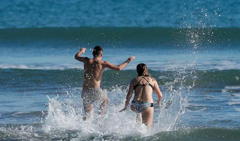 Una pareja se baña en la playa de la Malvarrosa.