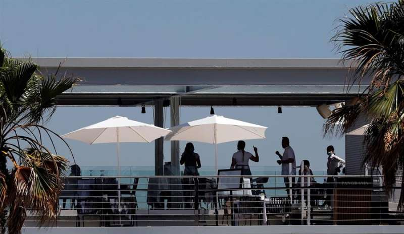 Una camarera atiende a unos clientes en la terraza de un restaurante. EFE