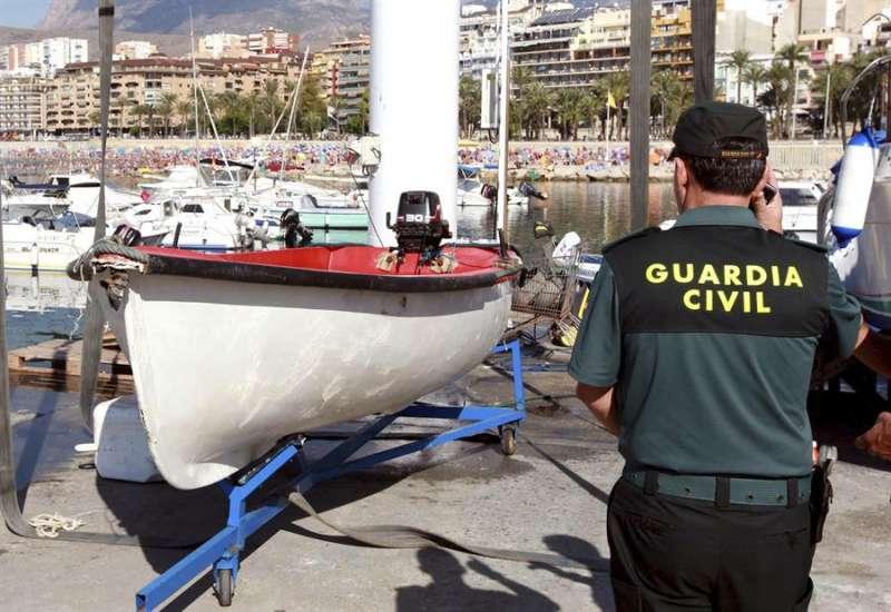 Imagen de archivo de un agente de la Guardia Civil junto a una patera hallada en el litoral de Alicante. EFE