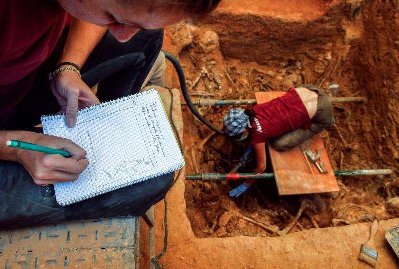 Una arqueóloga realiza un boceto de la fosa durante los trabajos de excavación en la fosa común 112 del cementerio de Paterna (Valencia). EFE/Archivo