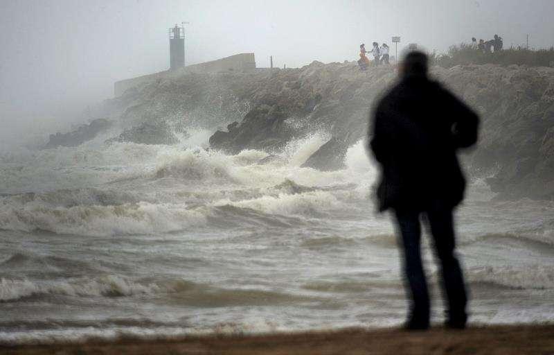 Varias personas contemplan la fuerte marejada junto al puerto de Gandia, en un temporal de lluvia. EFE/Archivo