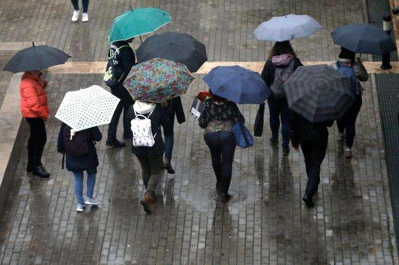 Varios jóvenes se protegen con paraguas hoy en València. EFE/Archivo