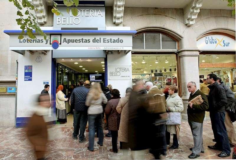 Colas que habitualmente se forman en Navidad en las administraciones de Lotería para adquirir décimos. EFE/Manuel Bruque/Archivo