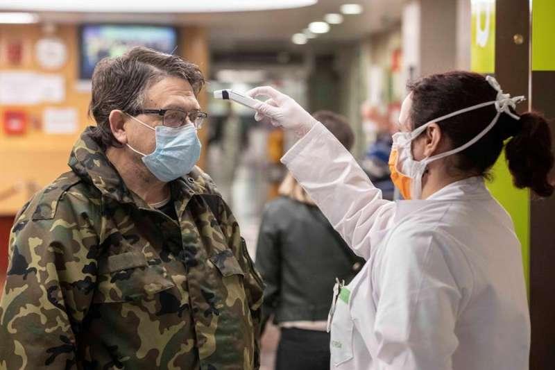 Una enfermera toma la temperatura a un hombre antes de la consulta con el médico. EFE