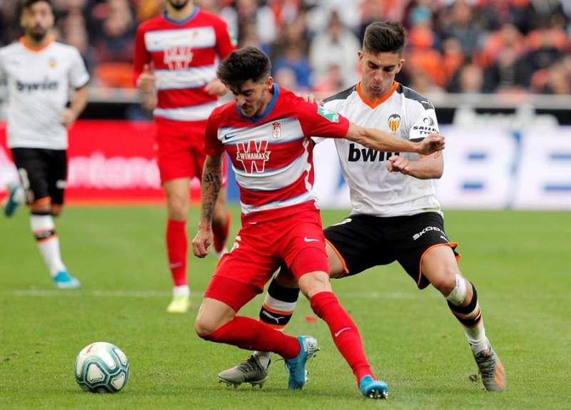 Ferran Torres (d) disputa el balón con el defensor del Granada Carlos Neva (i). EFE/Kai Försterling