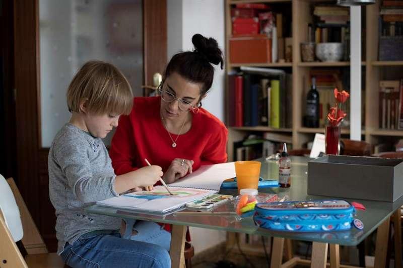 Una madre ayuda a su hijo a estudiar. EFE/Domenech Castelló