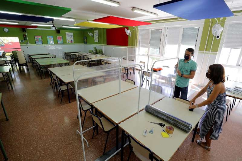 Dos responsables de un colegio de València acondicionan un aula.
