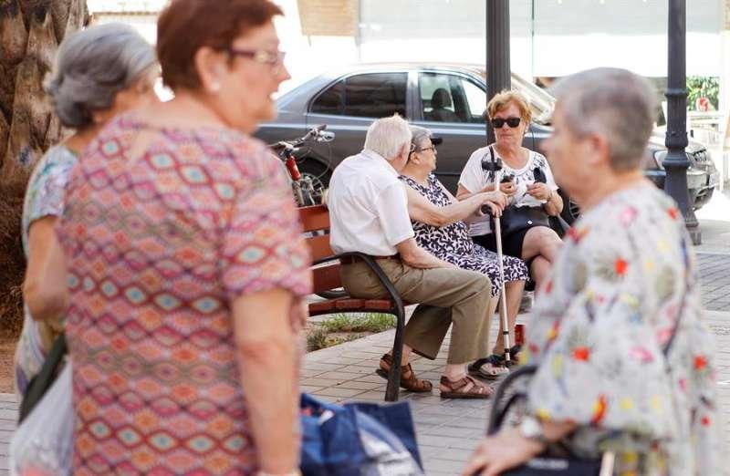 Un grupo de personas mayores conversa en la calle. EFE