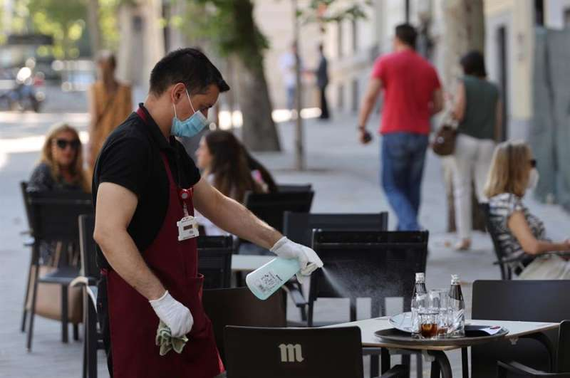 Un camarero desinfecta una mesa tras las marcha de los clientes. EFE