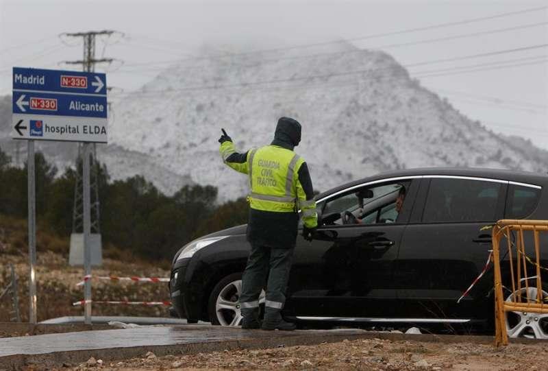 Agentes de la Guardia Civil de Tráfico indican a los conductores que la A-31 está cortada en la salida del hospital de Elda hacia Madrid. EFE/MORELL