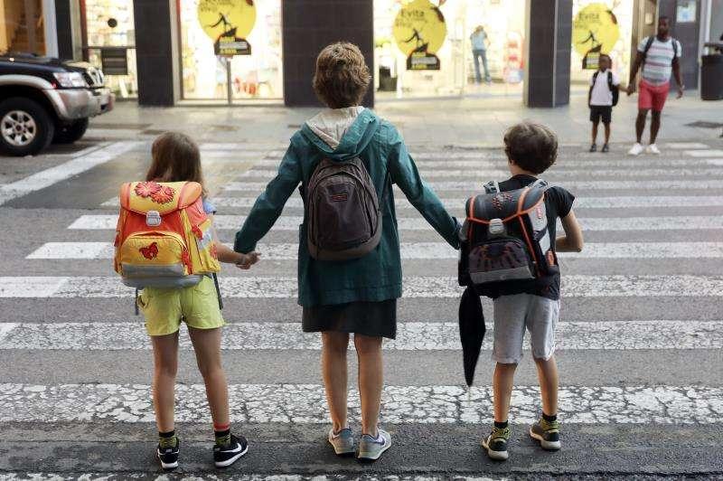 Una madre lleva a sus dos hijos al colegio durante el primer día de curso escolar. EFE/Archivo