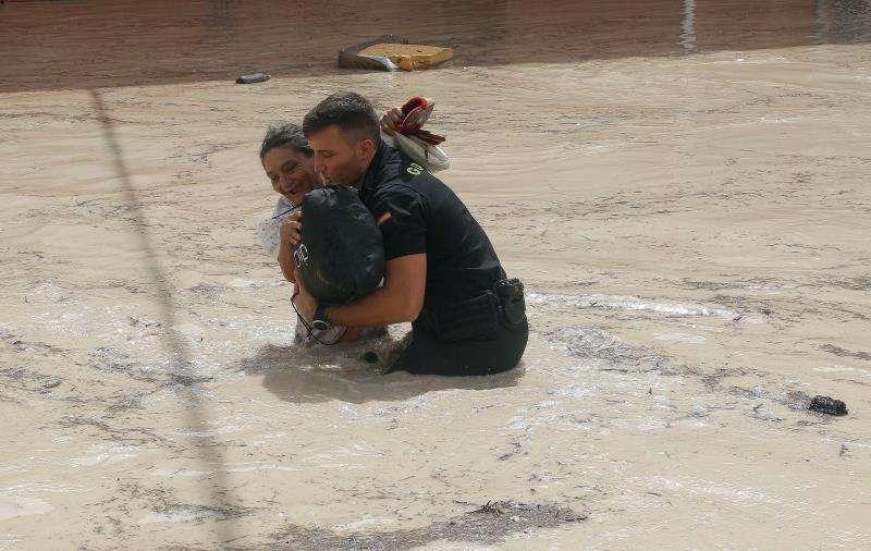 Un policía ayuda a una vecina de Almoradí este viernes tras la rotura del muro del cauce del río Segura por la crecida del río que ha provocado el desbordamiento a la entrada de la población. EFE/Morell