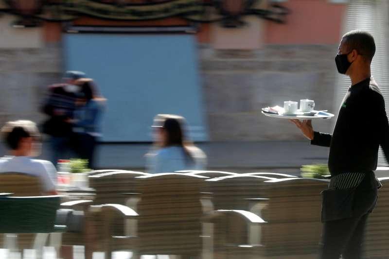 Un camarero sirve una mesa en el centro de València. EFE